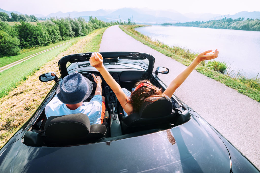 Two people driving a rental car on vacation