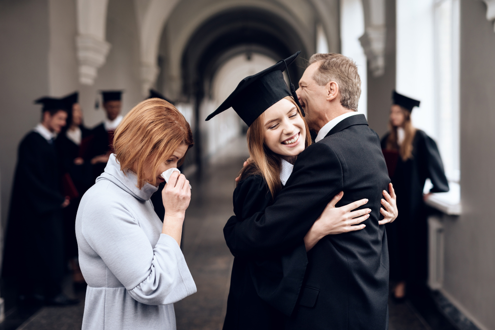 Parents hugging their graduate