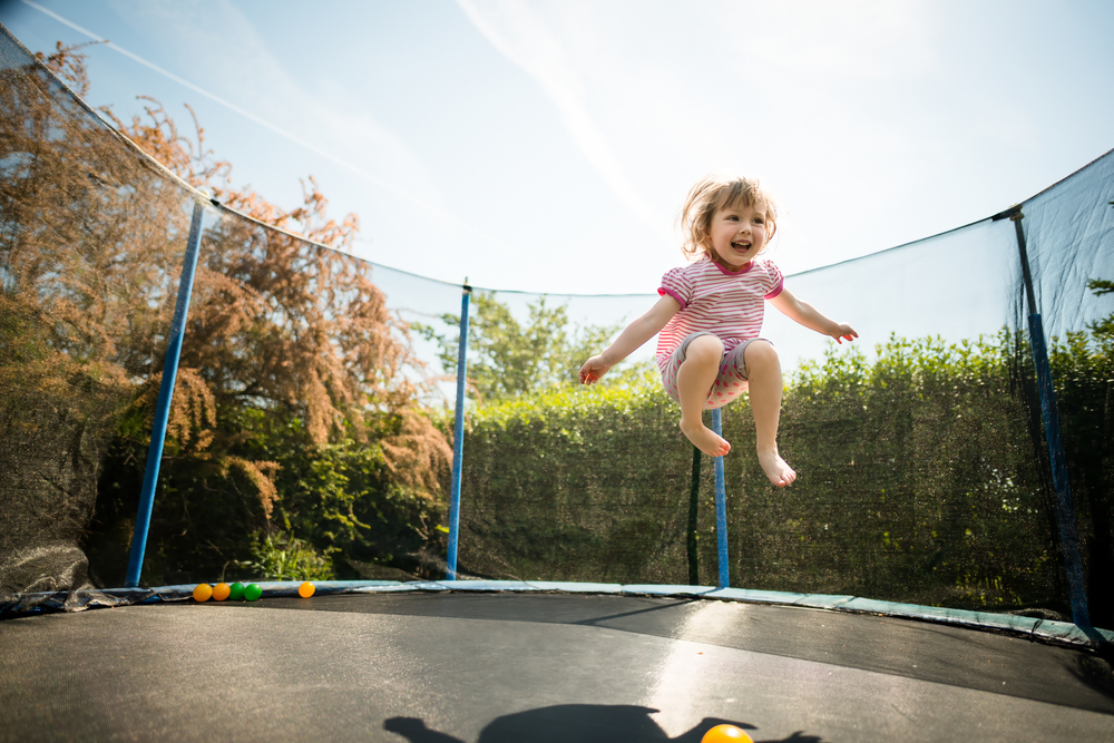 Small girl jumping on trampoline